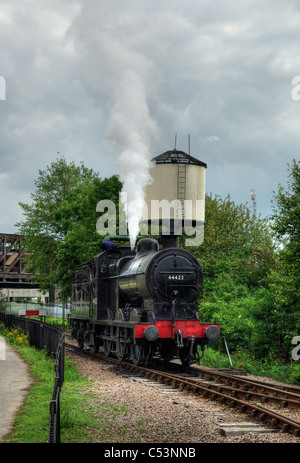 Train taking on water letting off steam at Peterborough station on the Nene Valley Railway. - Stock Photo