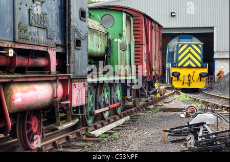 In the engine yard at Nene Valley Railway at Wansford, locomotives awaiting restoration, diesal engine in the background - Stock Photo