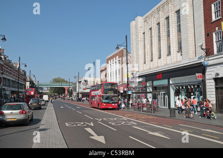 A red London bus waits at a bus stop in a general view of Brixton Road in central Brixton, London, UK. - Stock Photo
