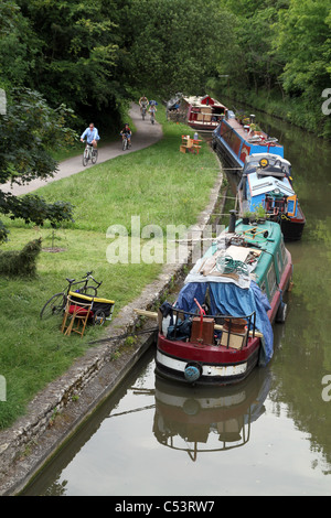 PEOPLE WALK AND CYCLE PAST BARGES ALONG THE KENNET AND AVON CANAL IN WILTSHIRE, ENGLAND, UK - Stock Photo