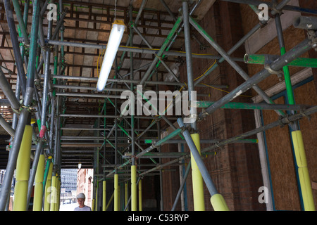 Overhead construction site scaffolding and a neon light above a young worker. - Stock Photo