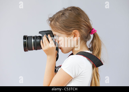 seven-year old girl who uses a digital SLR - Stock Photo