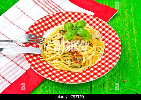 Spaghetti with pesto, made from dried tomatoes, Grana, pecorino, arugula, basil, pine nuts and garlic - Stock Photo