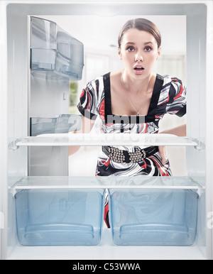 Young woman looking on empty shelf in fridge. - Stock Photo