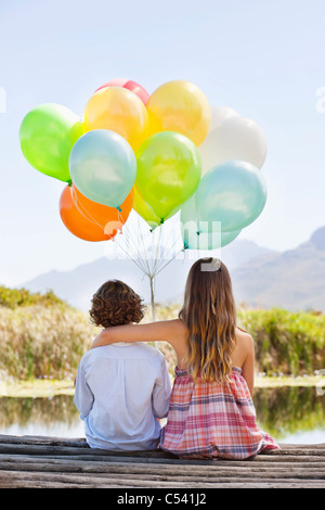Rear view of siblings playing with balloons at a pier - Stock Photo