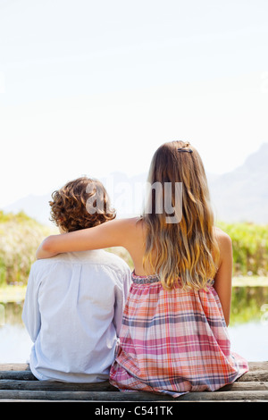 Rear view of siblings sitting together at a pier - Stock Photo