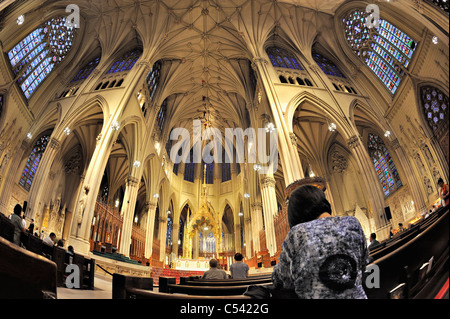 St. Patrick's Cathedral with woman kneeling in pew from behind, domed main altar, Manhattan NYC 2011-06-27 (fisheye - Stock Photo