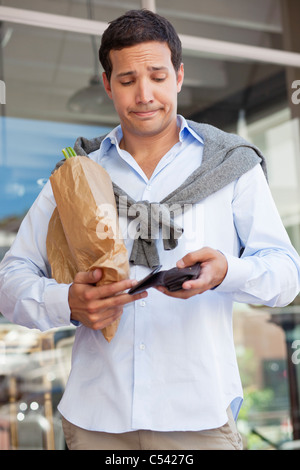 Mid adult man checking the empty wallet with paper bag full of vegetables - Stock Photo