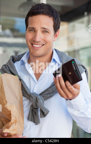 Portrait of a man showing empty wallet with paper bag full of vegetables - Stock Photo