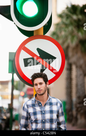 Man with 'No Entry' sign and traffic light in the background - Stock Photo
