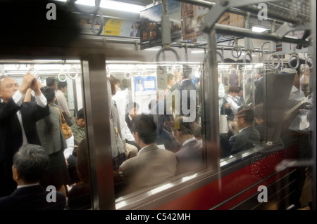 Passengers traveling in a subway train, Tokyo, Japan - Stock Photo