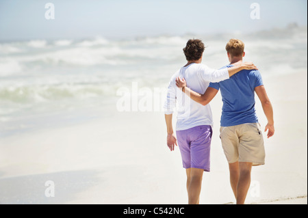 Rear view of two men walking with their arms around each other - Stock Photo