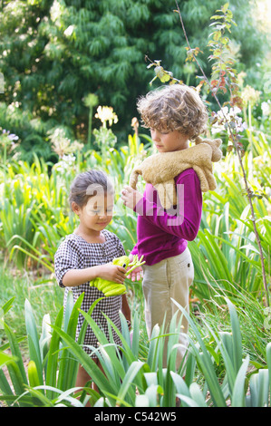 Cute little boy standing with little girl in a garden - Stock Photo