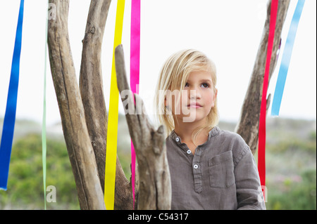 Girl standing near a tree decorated with ribbon - Stock Photo