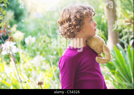 Side profile of a little boy looking away in a garden - Stock Photo