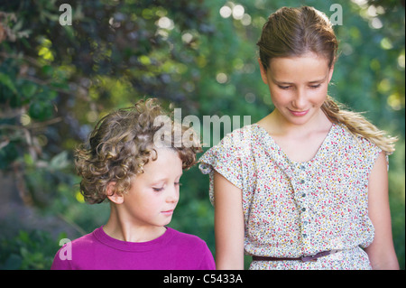 Cute little siblings walking together in a garden - Stock Photo