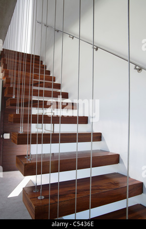 Wooden staircase with white walls and metal railing - Stock Photo