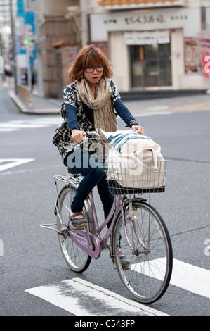 Woman riding a bicycle, Tokyo, Japan - Stock Photo