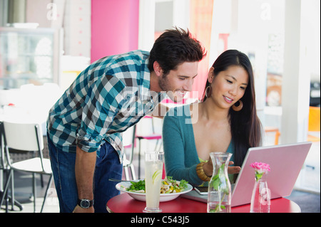 Woman using a laptop with her friend in a restaurant