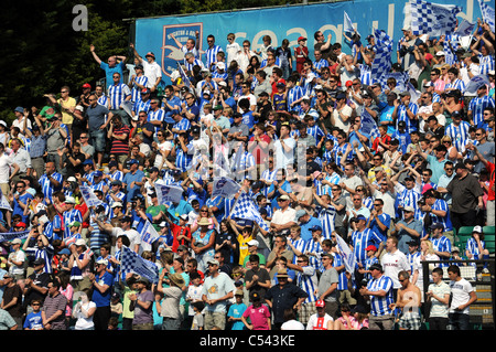Brighton and Hove Albion football fans cheer their team on to the pitch at the Withdean stadium - Stock Photo