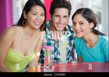 Portrait of a man and women with lime juice on table in a restaurant - Stock Photo