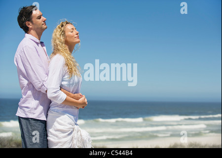 Man embracing a woman from behind on the beach - Stock Photo