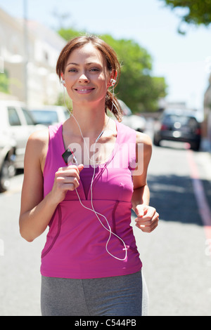 Beautiful young woman listening to mp3 player while jogging - Stock Photo