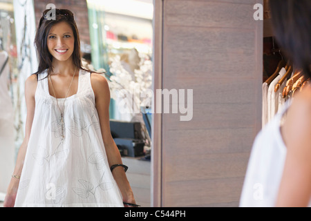 Portrait of a beautiful young woman trying on a dress in a mirror - Stock Photo