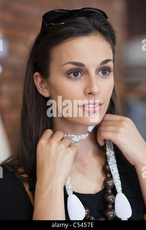 Young woman trying a necklace in a mall - Stock Photo