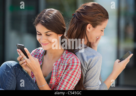 Two young women sitting back to back and text messaging - Stock Photo