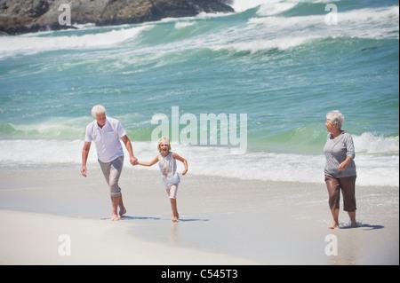Senior couple enjoying on the beach with their granddaughter - Stock Photo