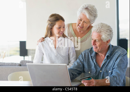 Senior man doing home shopping with a credit card with his family near him - Stock Photo