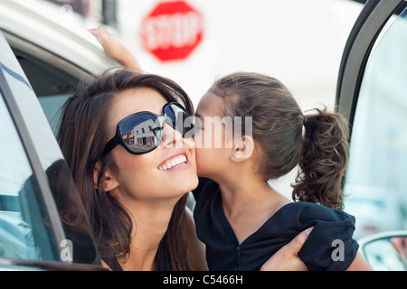 Beautiful young woman with her cute little daughter kissing in a car - Stock Photo