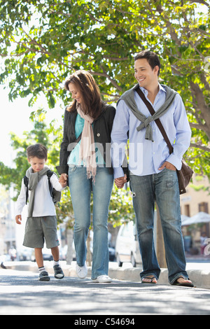 Family walking together on the road - Stock Photo