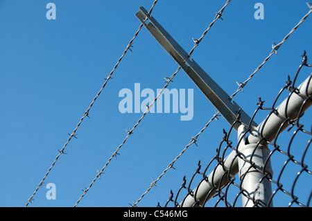 Low angle view of a portion of a chain-link fence with rows of barbed wire above it against a clear blue sky. - Stock Photo