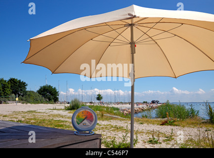A sunny July afternoon on the beach. A sun shade makes the UV index reading on the portable sun UV station fall - Stock Photo