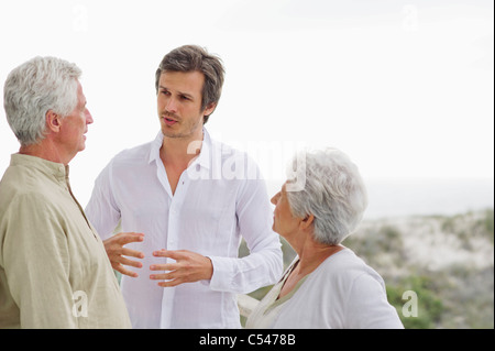 Mid adult man discussing to his parents - Stock Photo