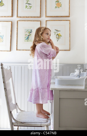 Cute little girl standing on a chair in front of a bathroom sink - Stock Photo