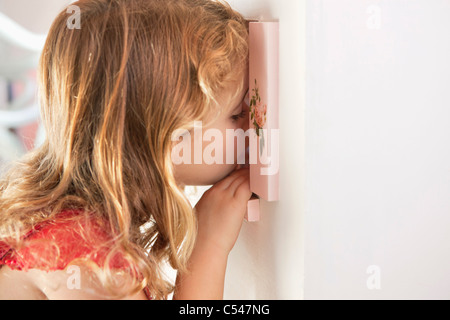 Cute little girl peeking into a dollhouse through the window - Stock Photo