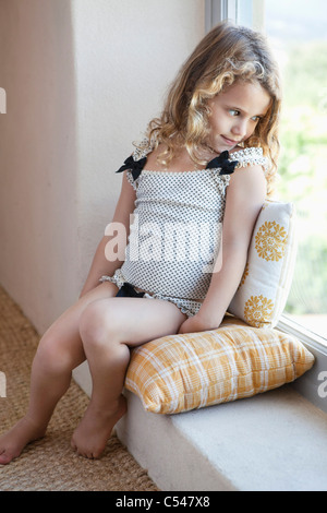 Cute little girl looking out from a window - Stock Photo
