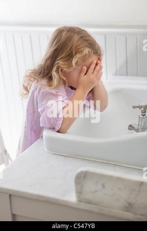 Cute little girl washing face in bathroom sink - Stock Photo