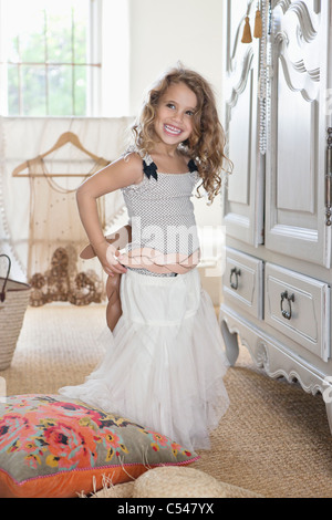 Cute little girl getting dressed like her mother in oversized clothes - Stock Photo
