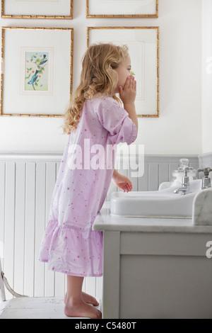 Cute little girl washing face in a bathroom - Stock Photo