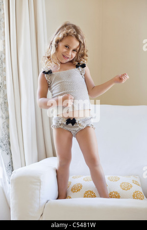 Portrait of a cute little girl playing air guitar - Stock Photo