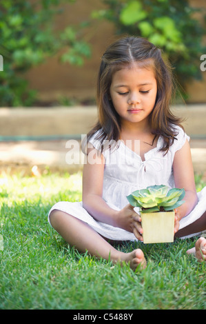 Cute little girl holding a potted plant - Stock Photo