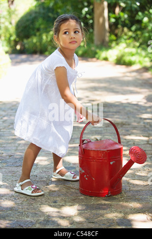 Cute little girl holding a watering can - Stock Photo