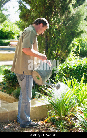 Side profile of a mature man watering plants in a garden - Stock Photo