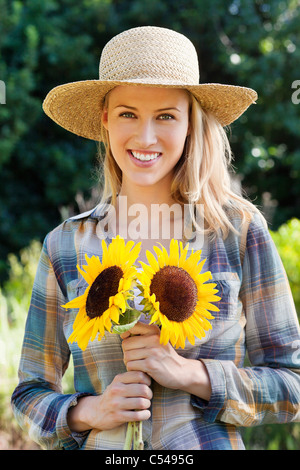 Portrait of a young woman holding sunflowers in a field - Stock Photo