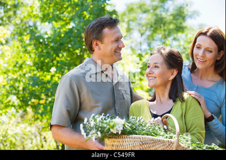 Woman standing with his son and daughter in law while holding basket of flowers - Stock Photo