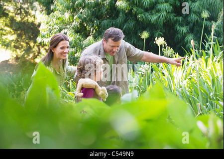 Two little children walking in a garden with their parents - Stock Photo